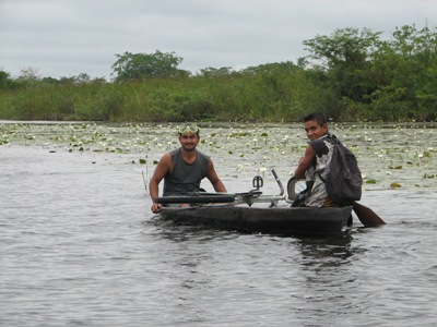 Men paddling a dugout canou with a bicycle on the New River, Belize