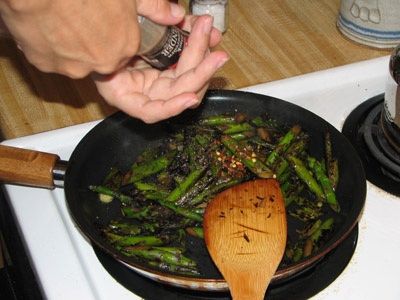 adding pepper to asparagus